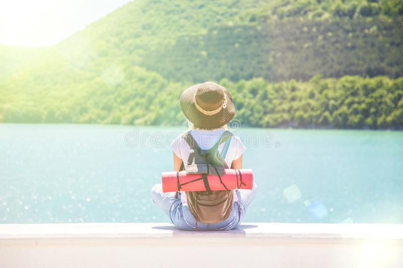 Pretty young woman tourist sits on a mountain lake on a sunny day The girl looks in a beautiful distance. View from back of the to royalty free stock photos