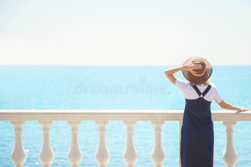 Pretty young woman tourist standing by the sea on a sunny day The girl looks in a beautiful distance. View from back of the touris stock photos