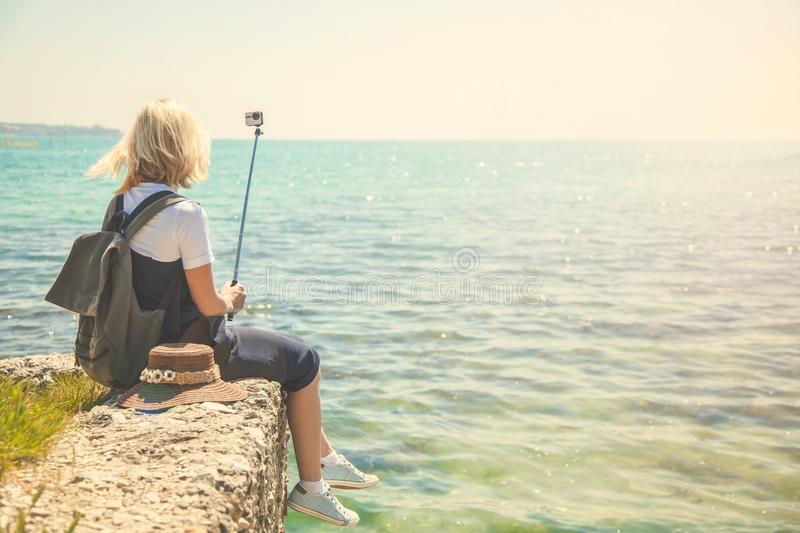 Pretty young woman tourist takes selfie portrait at the seashore on a sunny day Girl takes photo for travel blog. View from back o stock images