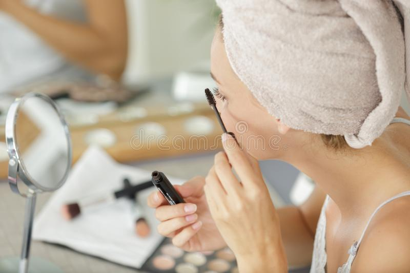 Pretty young woman with towel on head applying mascara stock image