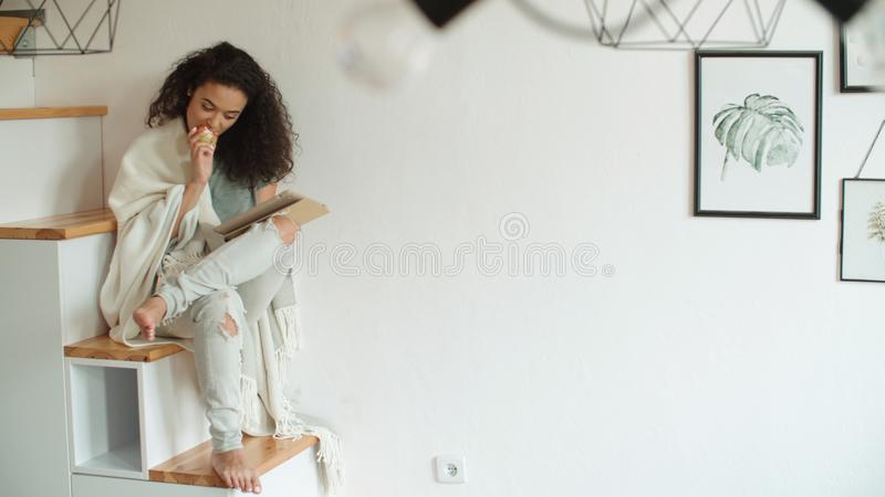 Pretty young woman using digital tablet at home. Pretty young woman using digital tablet and eating apple royalty free stock photos