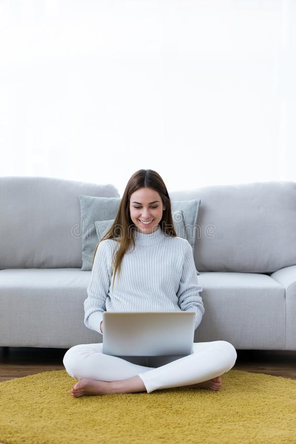 Pretty young woman using her laptop while sitting on the floor at home. royalty free stock photos