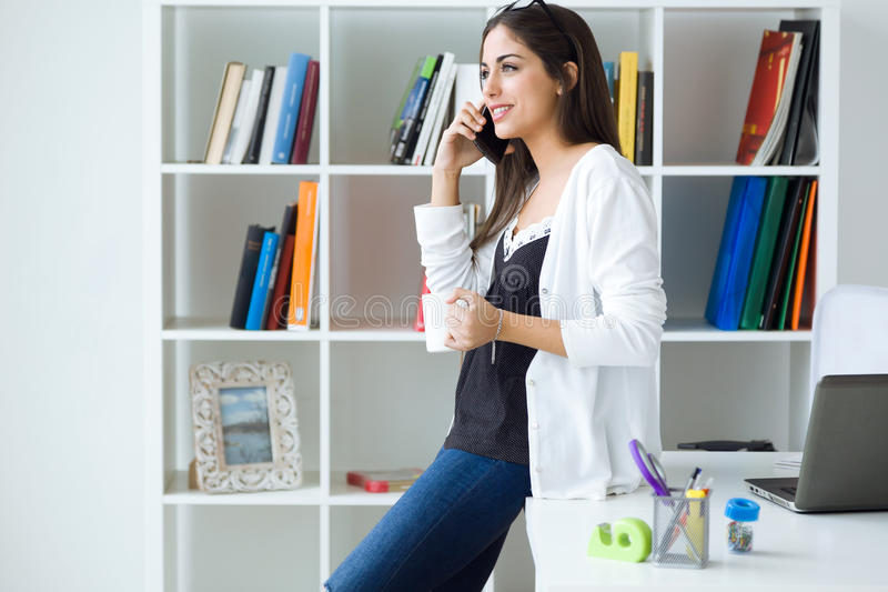 Pretty young woman using her mobile phone in the office. stock photography