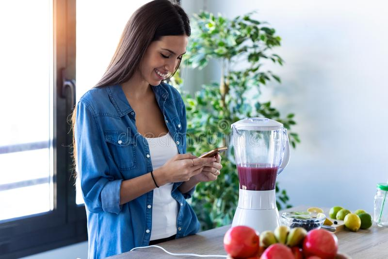 Pretty young woman using her mobile phone while preparing fruit smoothie in the kitchen at home stock image