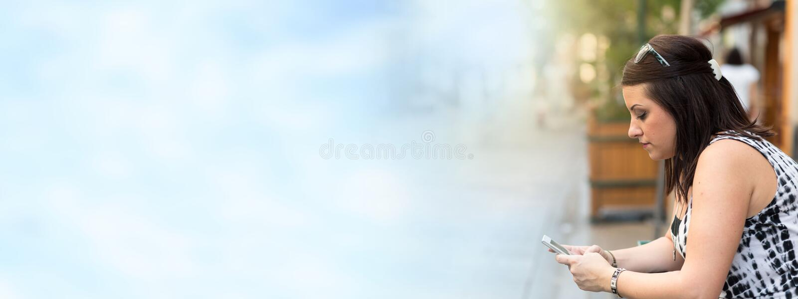 Pretty young woman using her mobile phone in the street royalty free stock photo
