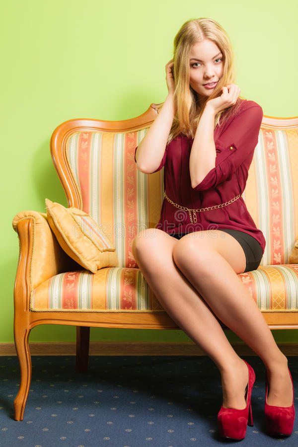 Pretty young woman on vintage sofa. Fashion. stock photography