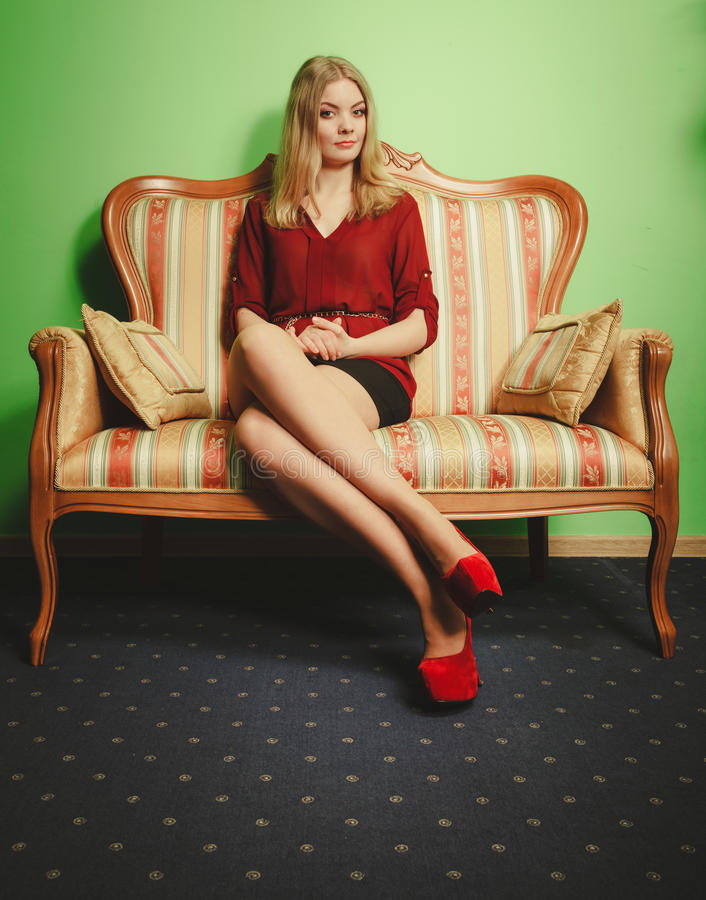 Pretty young woman on vintage sofa. Fashion. royalty free stock images