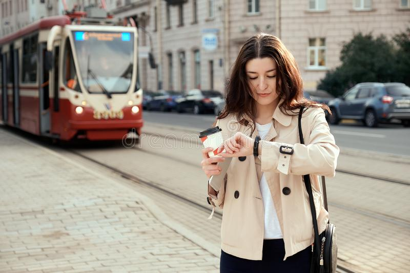 Pretty young woman waiting for train or tram as arrival, checking the time on smartwatch, drinking takeout coffee cup. royalty free stock image