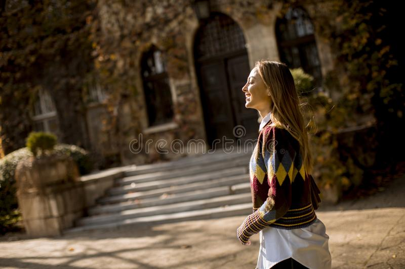 Pretty young woman walking in the autumn park royalty free stock photo