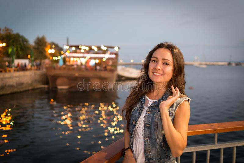 Pretty young woman walking on city promenade near sea in the evening royalty free stock photography