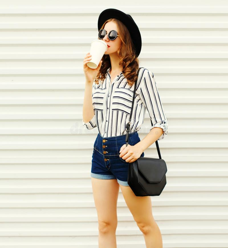 Pretty young woman walking with coffee cup in black round hat, shorts, white striped shirt on white wall. Background royalty free stock photo