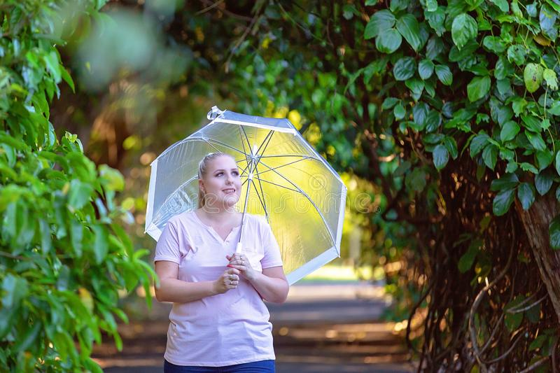 Young Woman Walking In Forest With Umbrella. Pretty young woman walking in forest gardens holding see through umbrella with yellow light in background stock images