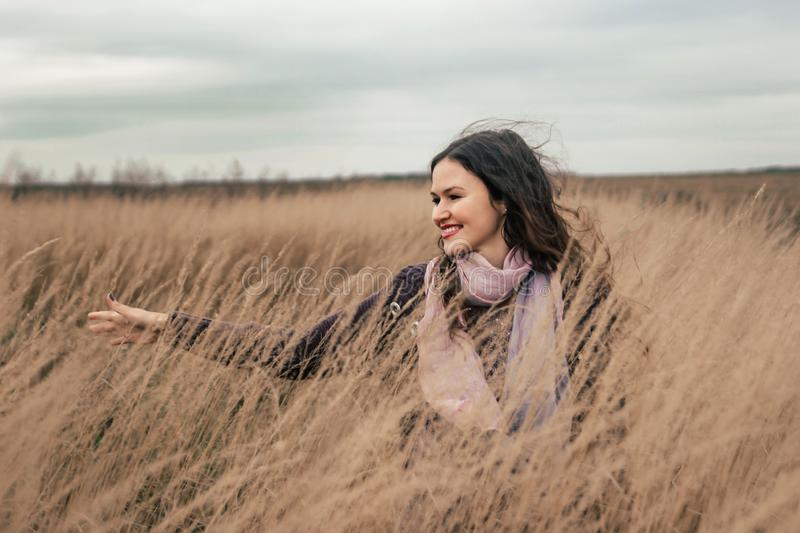 Pretty young woman walking on a wheat field royalty free stock photo