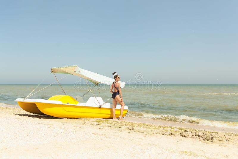 Pretty young woman wearing black swimsuit and sunglasses posing on the catamaran stock photos
