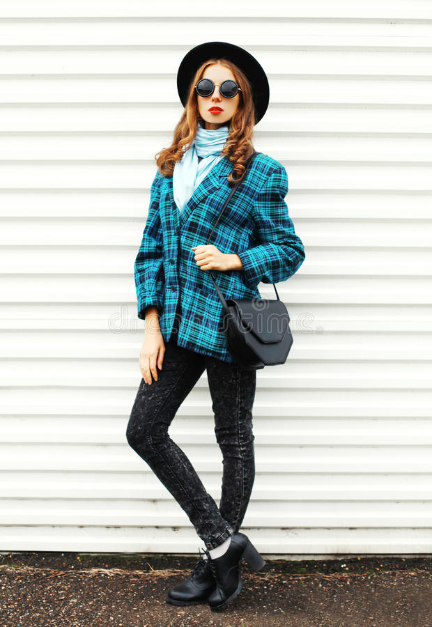 Pretty young woman wearing fashion black hat checkered coat jacket handbag walking in city over white. Background stock image