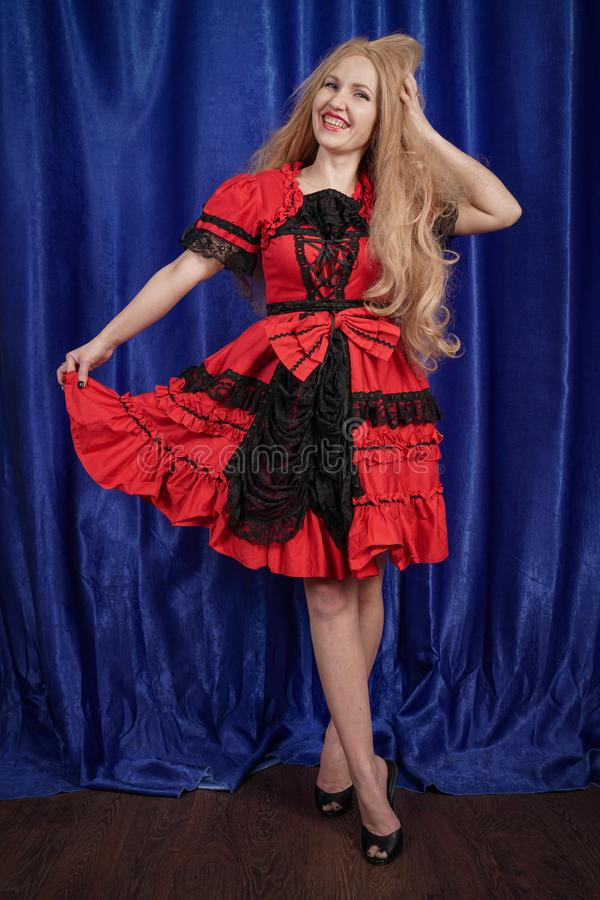 Pretty young woman wearing red faitytale halloween dress on blue background stock photo