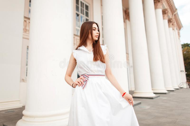 Pretty young woman in white fashionable dress posing near column. royalty free stock photography