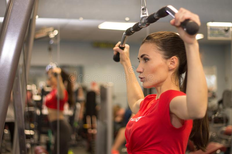 Pretty young woman working out in gym lifting weights stock images