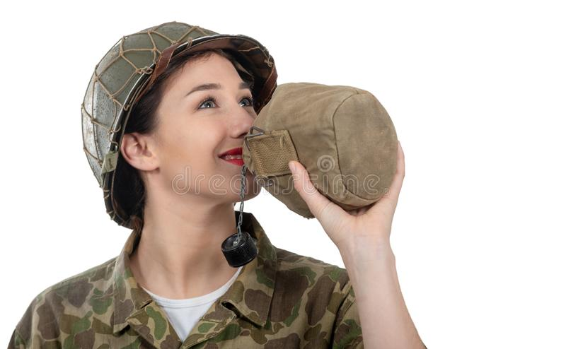 Pretty young woman in ww2 american uniform drinking water on the white background. Pretty young woman in ww2 american uniform drinking water isolated on the stock images