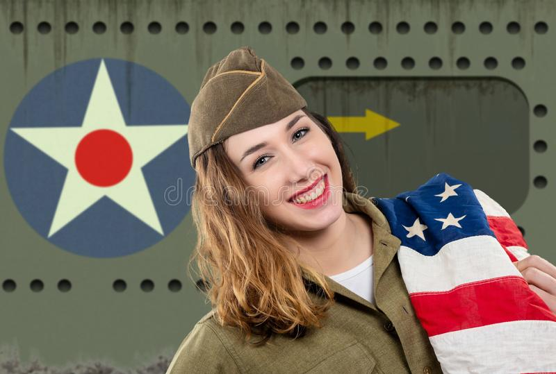 Pretty young woman in ww2 uniform us with american flag. A pretty young woman in ww2 uniform us with american flag stock photography