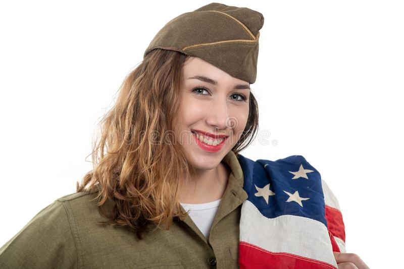 Pretty young woman in ww2 uniform us with american flag. Pretty young woman in ww2 uniform us with an american flag stock images