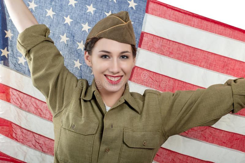 Pretty young woman in ww uniform us with american flag. A pretty young woman in ww uniform us with american flag royalty free stock photo