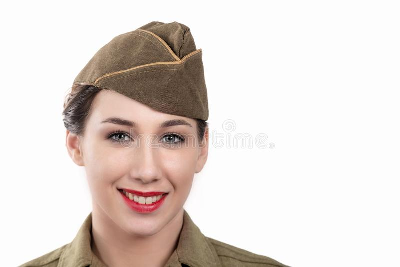 Pretty young woman in ww2 uniform us with garrison cap on white. A pretty young woman in ww2 uniform us with garrison cap on white background stock photography