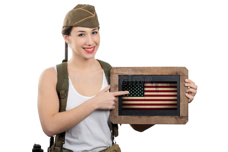 Pretty young woman in ww2 uniform us showing american flag. Pretty young woman in ww2 uniform us showing an  american flag stock image