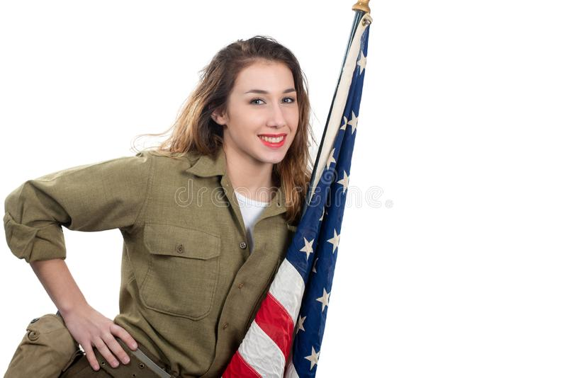 Pretty young woman in wwii uniform us with american flag. Pretty young woman in wwii uniform us with an american flag royalty free stock photography