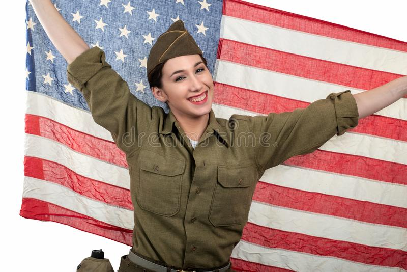 Pretty young woman in wwii uniform us with american flag. Pretty young woman in wwii uniform us with an american flag stock photography