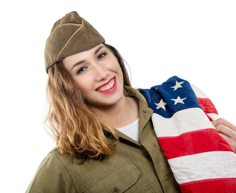 Pretty young woman in wwii uniform us with american flag. Pretty young woman in wwii uniform us with an american flag royalty free stock images