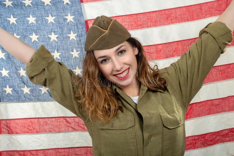 Pretty young woman in wwii uniform us with an american flag. A pretty young woman in wwii uniform us with an american flag royalty free stock images