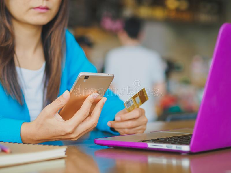 Pretty Young womans hands holding a credit card and using smartphone for online shopping. Online payment. Female working on laptop in a cafe royalty free stock images