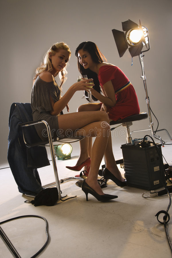 Pretty young women drinking. Pretty young women sitting with studio lights drinking wine and laughing stock image