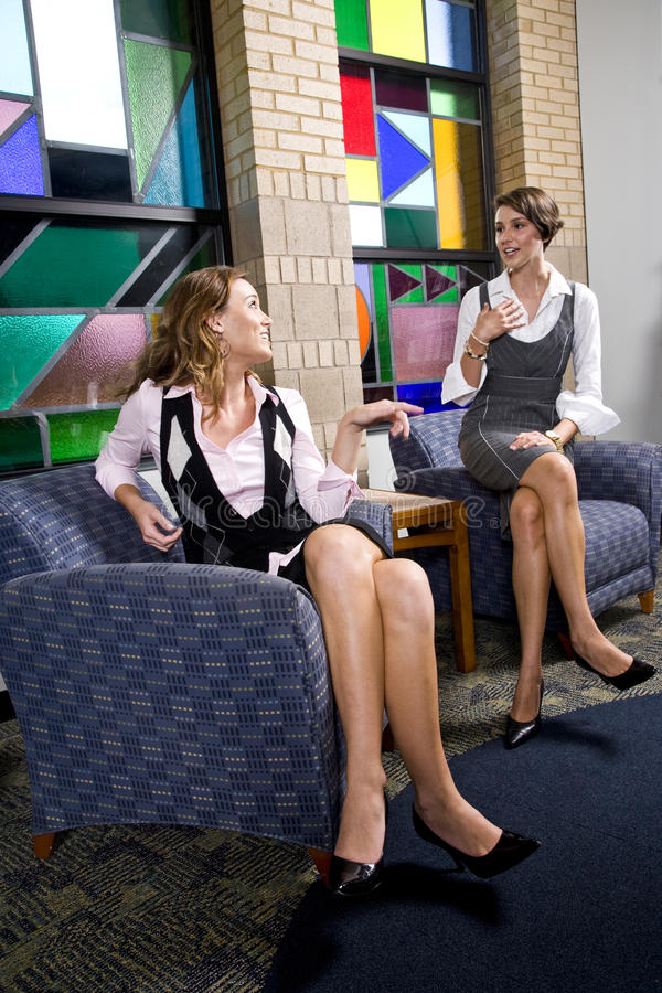Pretty young women sitting on waiting room chair royalty free stock photo