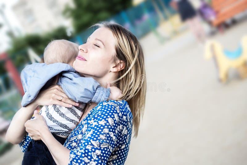 Prettyl gelukkige mather die met babyjongen hem omhelzen emotioneel op het houden van stock fotografie