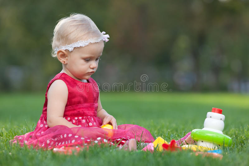 Prettylittle girl is playing with toy pyramid