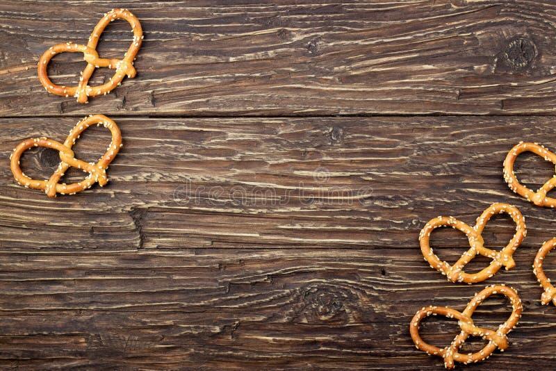 Pretzeis com as sementes de sésamo na tabela de madeira Alimento nacional alemão imagens de stock royalty free