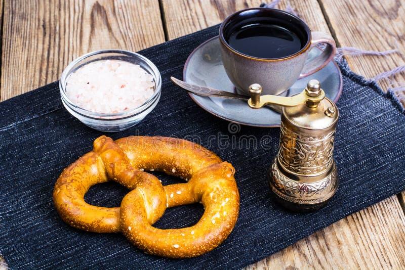 Pretzeis com sal e café preto no fundo de madeira fotos de stock