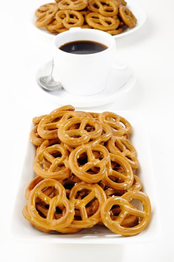 Pretzeis e copo de café salgados no branco fotos de stock royalty free