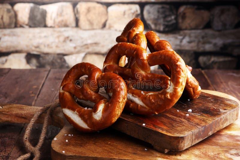 Pretzeis na placa de madeira no fundo rústico Alimento alemão imagem de stock