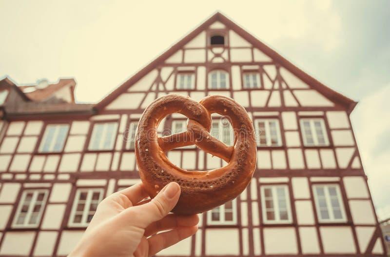 Pretzel à disposição do turista em Alemanha Casa bávara da cidade histórica e da pastelaria picante ou doce tradicional fotos de stock