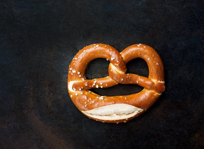 Pretzel saboroso alemão tradicional da lixívia com sal em Rusty Baking Tray Background rústico escuro Bandeira do cartaz para a p imagem de stock