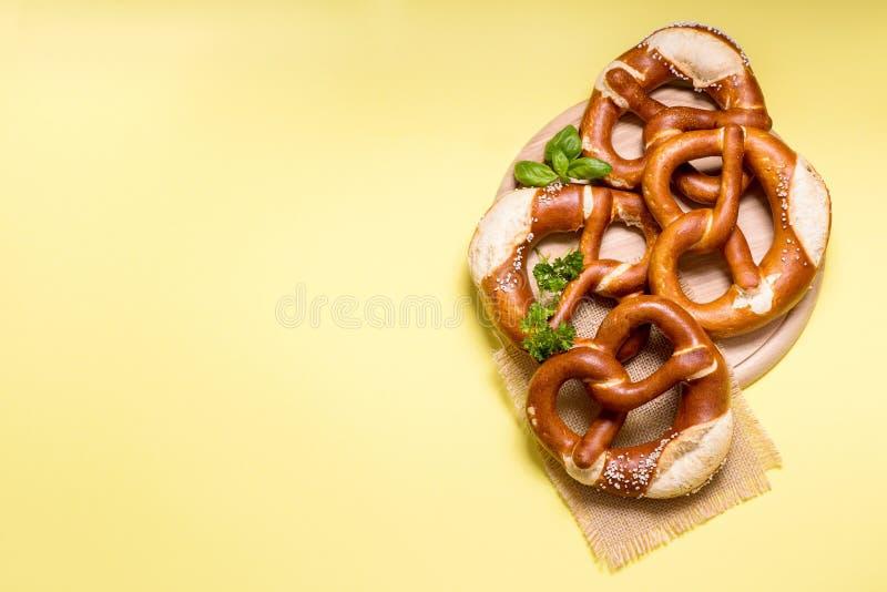 Pretzeles en el espacio amarillo de la copia del fondo, comida tradicional alemana fotografía de archivo
