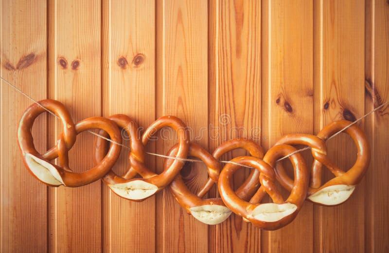 Pretzeles recientemente cocidos que cuelgan en cuerda para tender la ropa contra el tablero de madera Fondo para Oktoberfest fotos de archivo