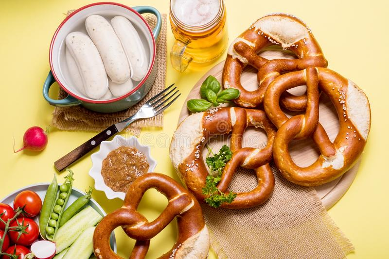 Pretzels, white bavarian sausages, mustard and beer, german traditional food, oktoberfest on yellow background royalty free stock image