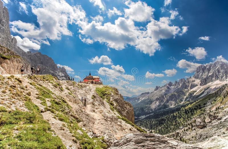 Preuss Refuge and trekkers at the foot of the Vajolet Towers. As seen from the trekking trail from Vajolet refuge to Principe pass royalty free stock photography