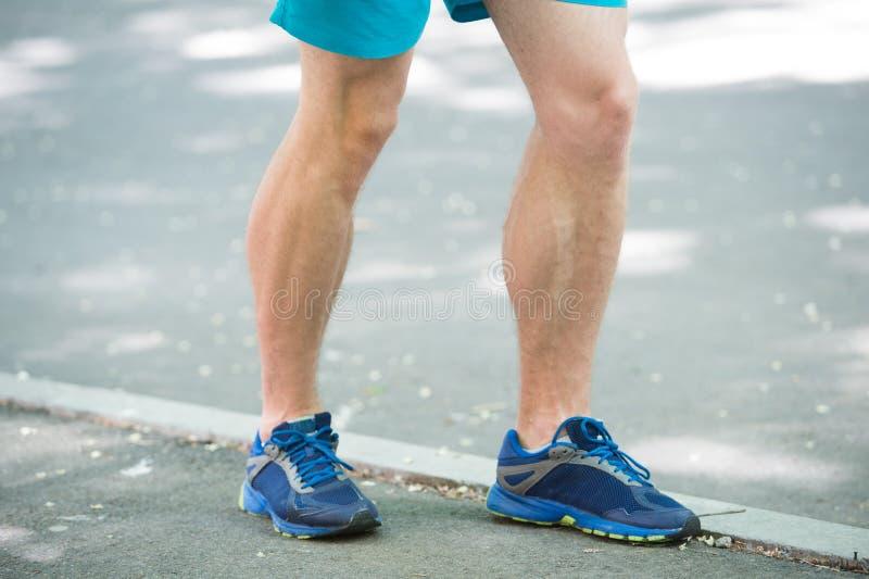 Prevent varicose concept. Legs of male athlete runner jogging park sidewalk. Training cardio in proper sport shoes. Vascular disease varicose veins problems stock photo