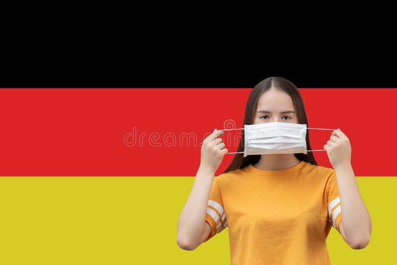 Preventie van het coronavirus in Duitsland Jonge meid zet een antibacterieel medisch masker op een vlaggenachtergrond met copyspa stock foto's