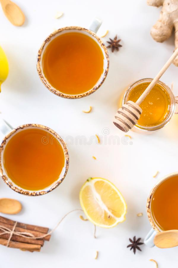 Preventing colds with vitamins. Tea with turmeric among products for improving immunity and treating colds - ginger, lemon, honey, anise. Top view, flat lay stock photography